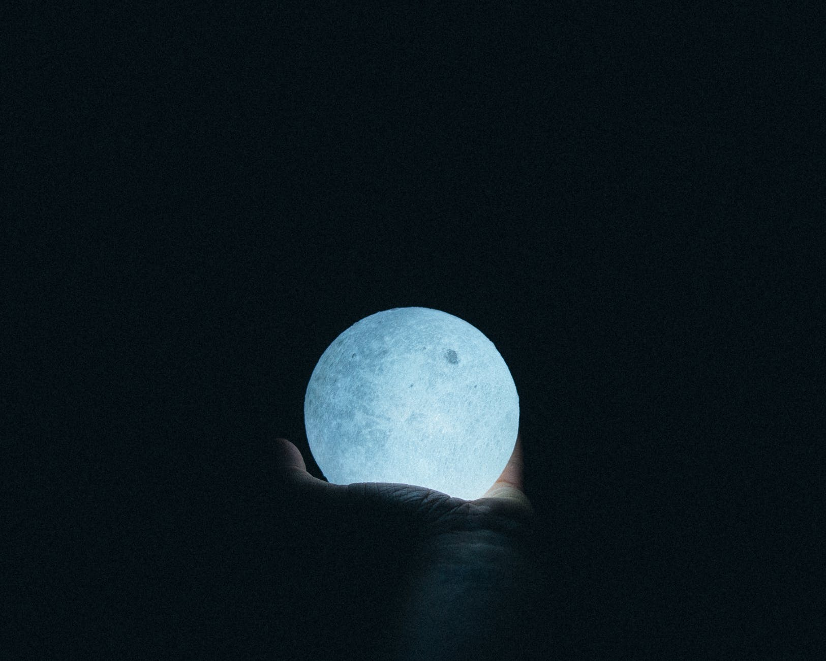 close up photo of person holding moon lamp