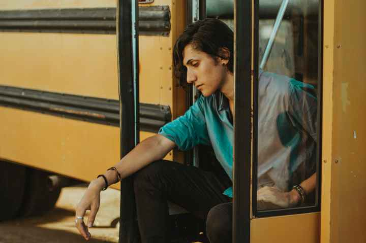 man sitting on door of school bus