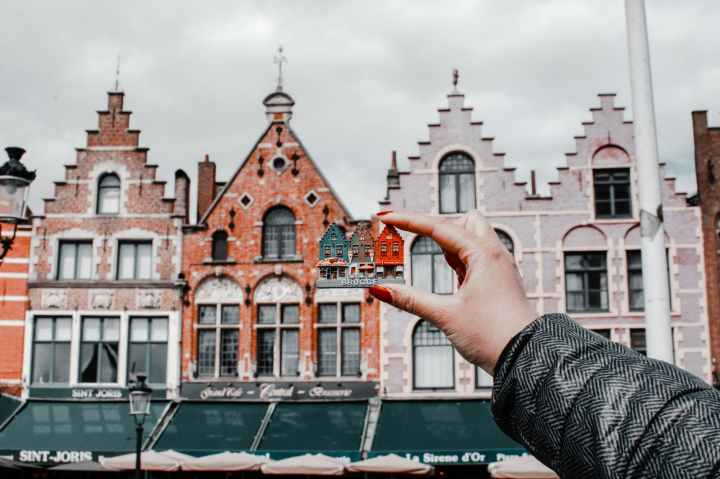 person holding miniature house toy comparing on real building