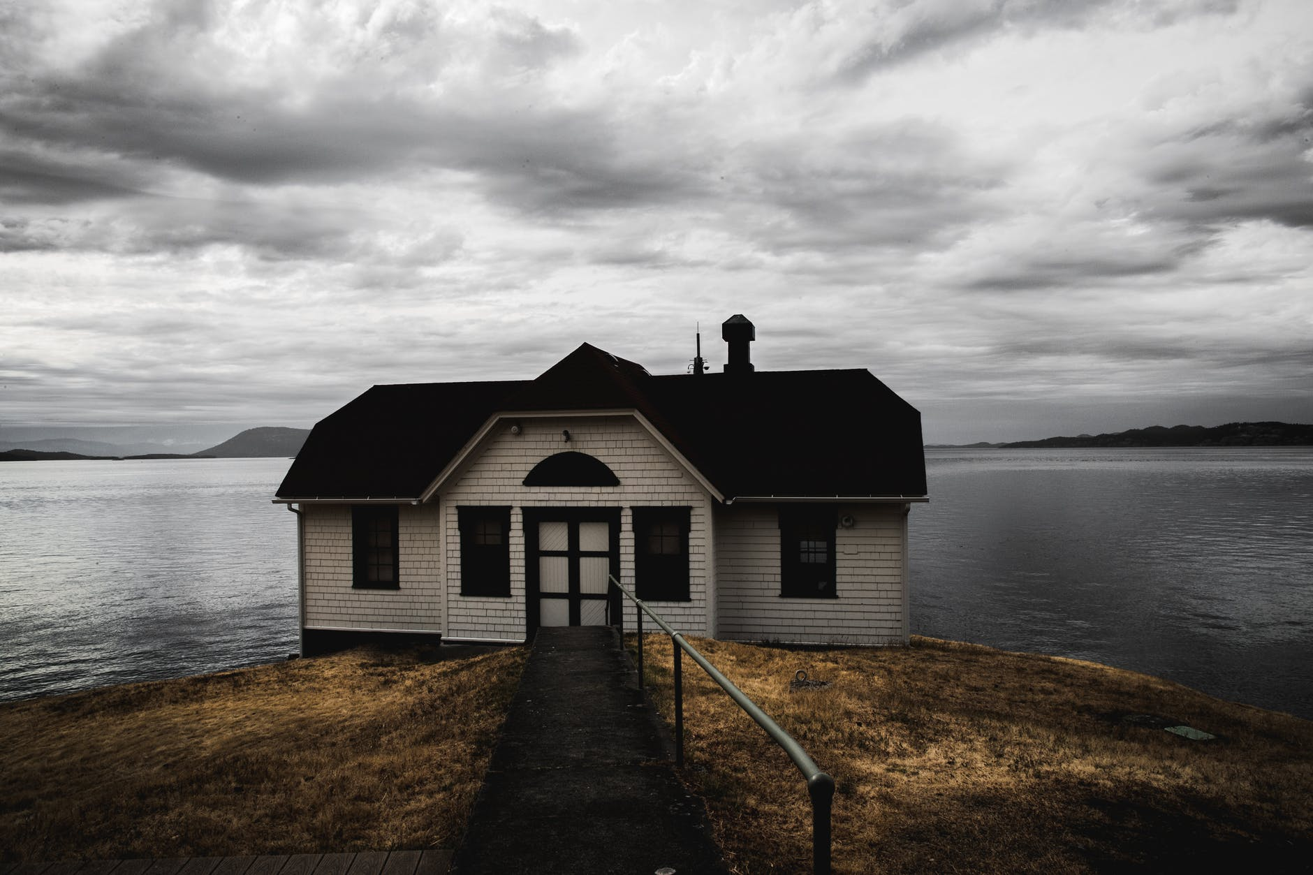 white and brown wooden house near calm body of water under cumulus clouds