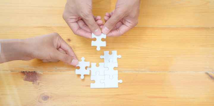 person holding white jigsaw puzzle piece